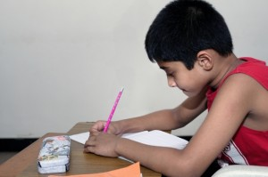 young indian boy writing